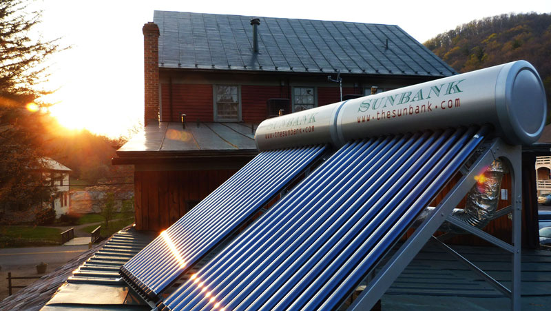 solar water heaters installed on the metal roof of a restaurant in virginia at sunset
