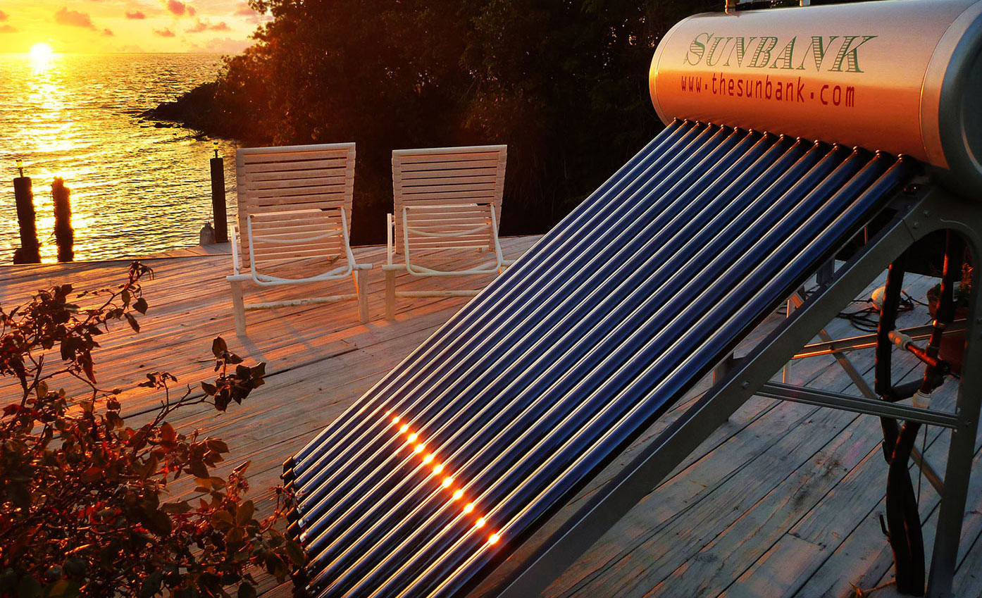 stand alone instllation of beautiful residential solar water heater ground mount installed on a deck in florida with water, sunset, and deck chairs behind it